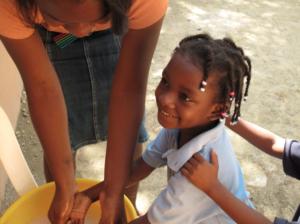 Qui a lato vedete una delle maestre che sta aiutando i bambini a lavarsi le manine prima di andare a mangiare.
